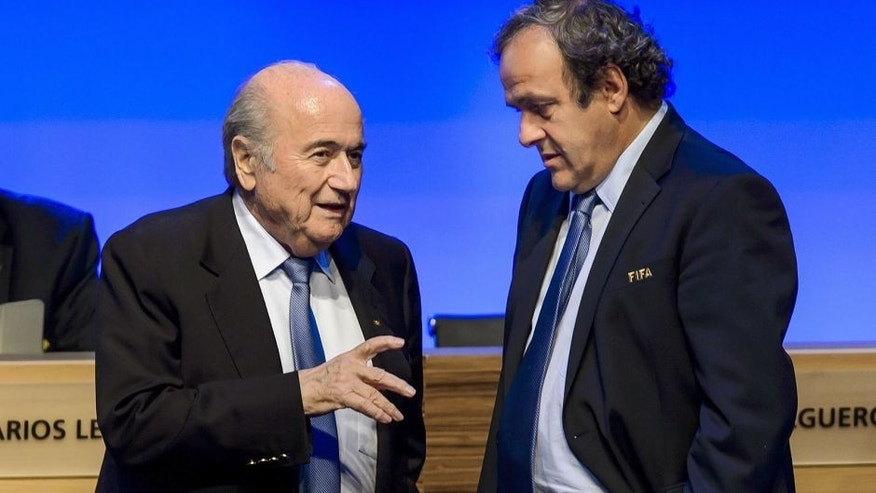 FIFA president Joseph Blatter talks to UEFA president Michel Platini during the 64th FIFA congress on June 11, 2014 in Sao Paulo, on the eve of the opening match of the 2014 FIFA World Cup in Brazil. AFP PHOTO / FABRICE COFFRINI (Photo credit should read FABRICE COFFRINI/AFP/Getty Images)
