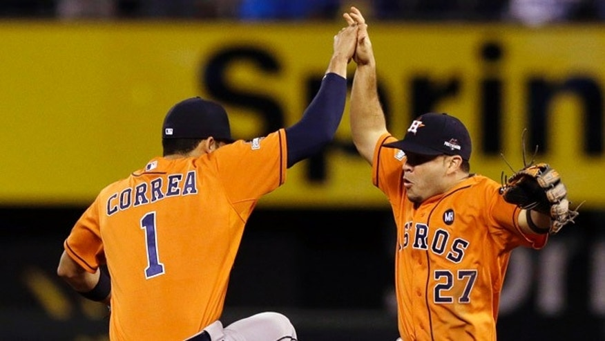 Houston Astros' Carlos Correa (1) celebrates with teammate Jose Altuve (27) after their 5-2 victory over the Kansas City Royals in Game 1 of baseball's American League Division Series, Thursday, Oct. 8, 2015, in Kansas City, Mo. (AP Photo/Orlin Wagner)
