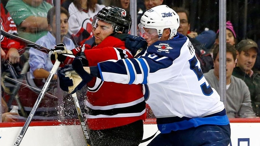 New Jersey Devils center Kyle Palmieri, left, is checked off the puck by Winnipeg Jets defensemen Tyler Myers (57) during the first period of an NHL hockey game in Newark, N.J., Friday, Oct. 9, 2015. The Jets defeated the Devils 3-1. (AP Photo/Rich Schultz)