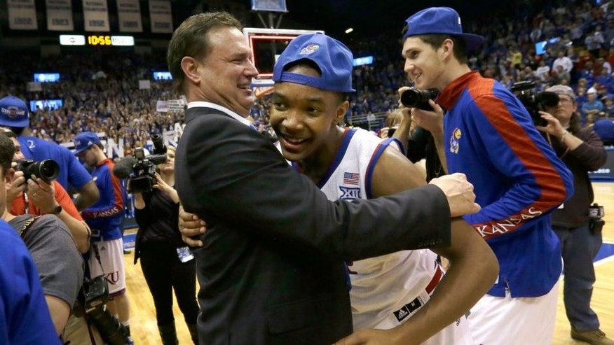 Kansas coach Bill Self, left, hugs guard Devonte Graham following an NCAA college basketball game against West Virginia at Allen Fieldhouse in Lawrence, Kan., Tuesday, March 3, 2015. Kansas defeated West Virginia 76-69 in overtime. (AP Photo/Orlin Wagner)