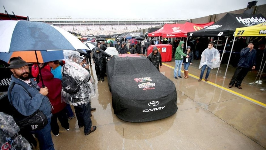 CHARLOTTE, NC - OCTOBER 10: The #18 M&M's Pretty In Pink Foundation Toyota of Kyle Busch sits covered in the rain prior to the NASCAR Sprint Cup Series Bank of America 500 at Charlotte Motor Speedway on October 10, 2015 in Charlotte, North Carolina. (Photo by Chris Graythen/NASCAR via Getty Images)