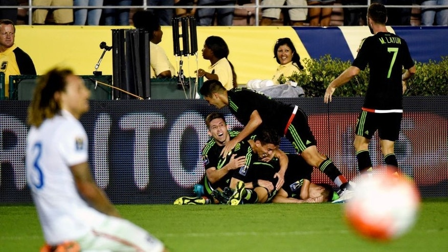 Paul Aguilar of Mexico celebrates with teammates after his game winning shot on goal as US player Jermaine Jones reacts during their 2015 CONCACAF Cup match at the Rose Bowl in Pasadena, California on October 10, 2015. The match is a playoff for the 2017 Confederations Cup. The United States lost to Mexico 3-2. AFP PHOTO / MARK RALSTON (Photo credit should read MARK RALSTON/AFP/Getty Images)