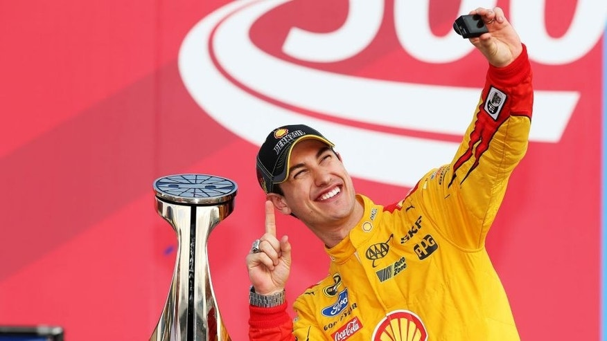 CHARLOTTE, NC - OCTOBER 11: Joey Logano, driver of the #22 Shell Pennzoil Ford, takes a 'selfie' in Victory Lane after winning the NASCAR Sprint Cup Series Bank of America 500 at Charlotte Motor Speedway on October 11, 2015 in Charlotte, North Carolina. (Photo by Chris Graythen/NASCAR via Getty Images)