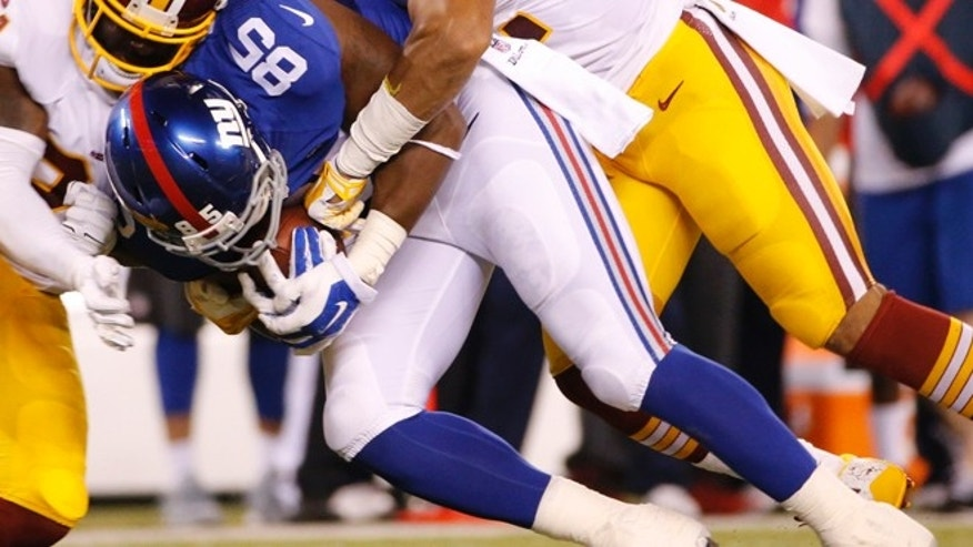 Washington Redskins strong safety Trenton Robinson and Keenan Robinson tackle New York Giants tight end Daniel Fells.