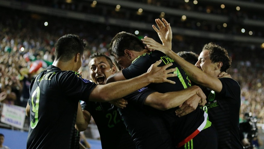 Mexicoâs Javier Hernandez is embraced by teammates after scoring his side's first goal against United States during the CONCACAF Cup soccer match at the Rose Bowl Stadium, in Pasadena , Calif. Saturday, Oct. 10, 2015. (AP Photo/Jae C. Hong)