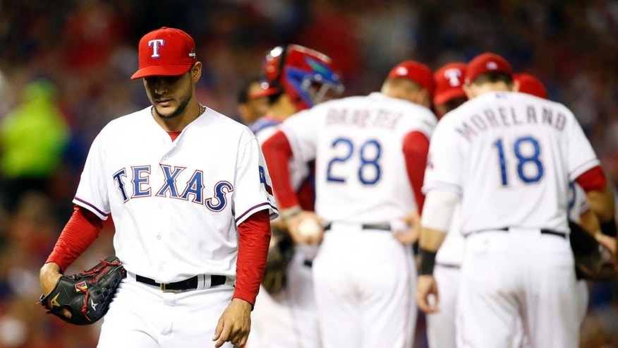 Oct 11, 2015; Arlington, TX, USA; Texas Rangers starting pitcher Martin Perez (left) walks to the dugout after being relieved against the Toronto Blue Jays in the 6th inning in game three of the ALDS at Globe Life Park in Arlington. Mandatory Credit: Tim Heitman-USA TODAY Sports