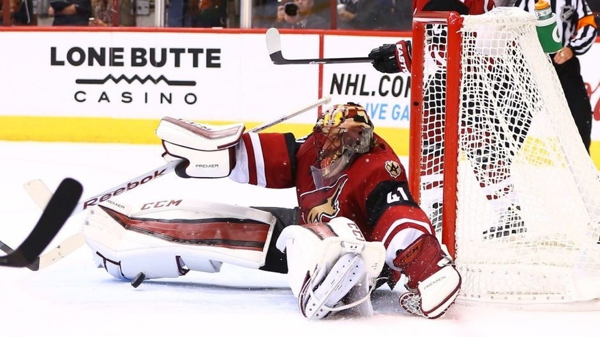 Oct 10, 2015; Glendale, AZ, USA; Arizona Coyotes goalie Mike Smith makes a save in the third period against the Pittsburgh Penguins during the home opener at Gila River Arena. The Coyotes defeated the Penguins 2-1. Mandatory Credit: Mark J. Rebilas-USA TODAY Sports