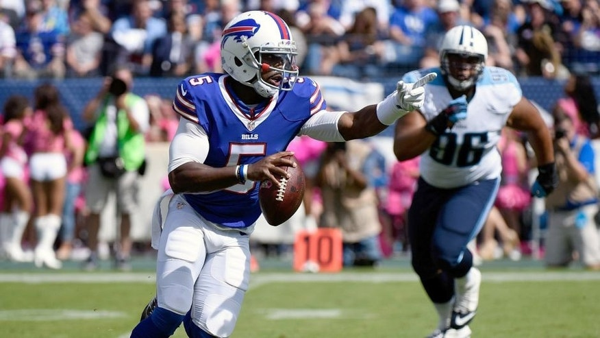 NASHVILLE, TN - OCTOBER 11: Quarterback Tyrod Taylor #5 of the Buffalo Bills rushes out of the reach of Al Woods #96 of the Tennessee Titans during the first half of a game at Nissan Stadium on October 11, 2015 in Nashville, Tennessee. (Photo by Frederick Breedon/Getty Images)