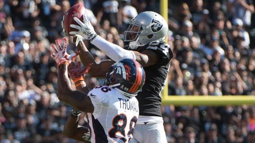 October 11, 2015; Oakland, CA, USA; Oakland Raiders free safety Charles Woodson (24) intercepts the football intended for Denver Broncos wide receiver Demaryius Thomas (88) during the third quarter at O.co Coliseum. The Raiders defeated the Broncos 16-10. Mandatory Credit: Kyle Terada-USA TODAY Sports