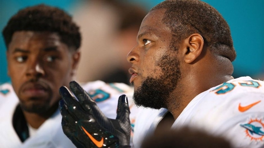 MIAMI GARDENS, FL - SEPTEMBER 27: Ndamukong Suh #93 of the Miami Dolphins talks with Cameron Wake #91 on the bench during the fourth quarter of the game against the Buffalo Bills at Sun Life Stadium on September 27, 2015 in Miami Gardens, Florida. (Photo by Rob Foldy/Getty Images)