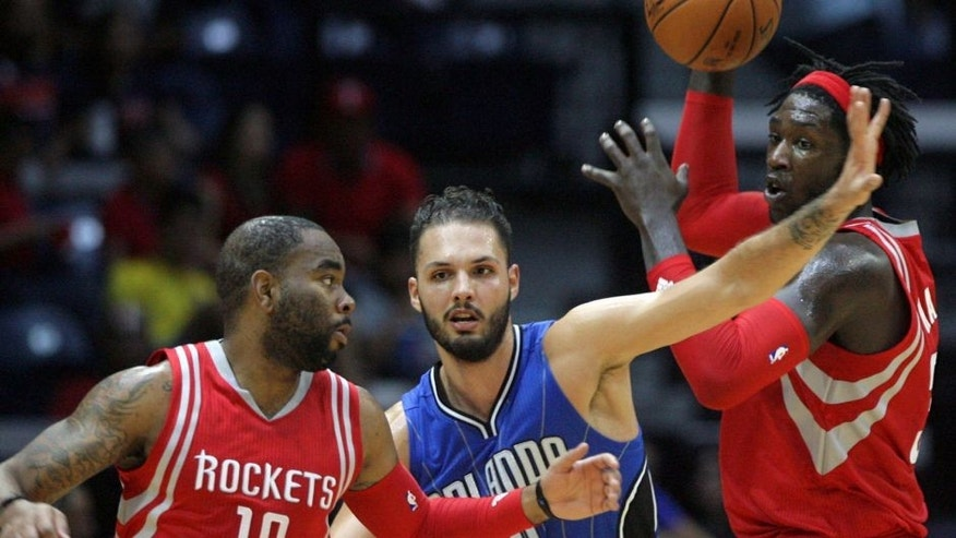 Houston Rockets Montrezl Harrell, right, looks for open teammate Marcus Thorton (10), as Orlando Magic Evan Fournier defends during the second half of a preseason NBA basketball game Sunday, Oct. 11, 2015, in Hidalgo, Texas. (AP Photo/Delcia Lopez)