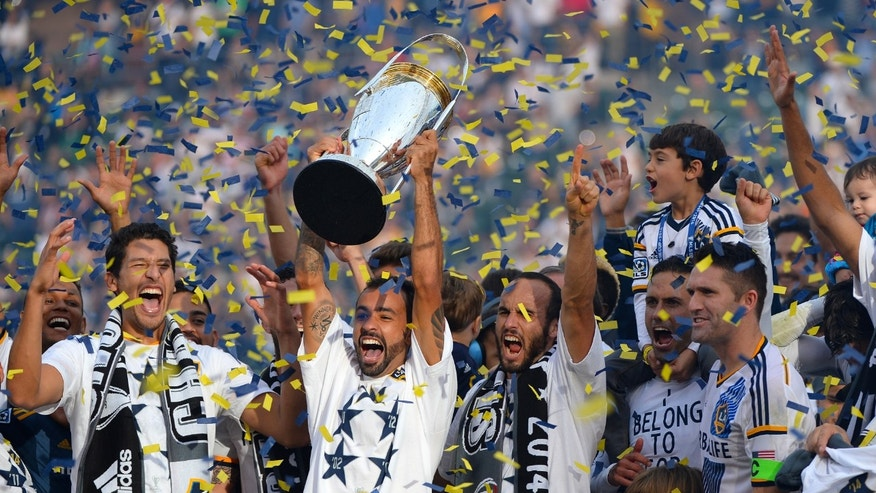 LOS ANGELES, CA - DECEMBER 07:  (left to right) Omar Gonzalez, Juninho, Landon Donovan and Robbie Keane of the Los Angeles Galaxy celebrate with the Phillip F. Anschutz Trophy after defeating the New England Revolution during the 2014 MLS Cup match at the at StubHub Center on December 7, 2014 in Los Angeles, California.  (Photo by Robert Laberge/Getty Images)
