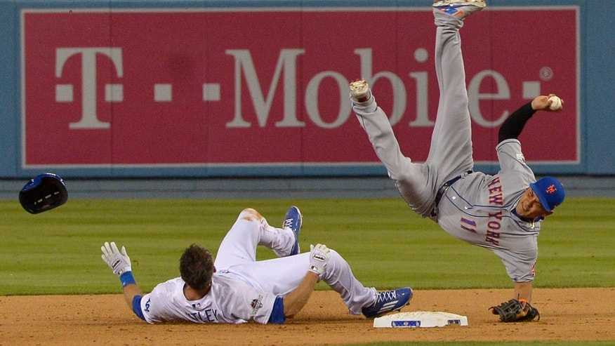 New York Mets shortstop Ruben Tejada falls after a slide by Los Angeles Dodgers' Chase Utley during the seventh inning of an NL Division Series baseball game Saturday, Oct. 10, 2015, in Los Angeles. (John McCoy/Los Angeles Daily News via AP)