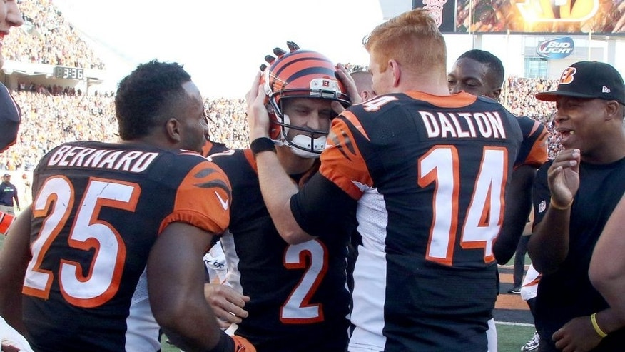 CINCINNATI, OH - OCTOBER 11: Mike Nugent #2 is congratulated by Giovani Bernard #25 and Andy Dalton #14, of the Cincinnati Bengals after kicking the game winning field goal in overtime to defeat the Seattle Seahawks 27-24 at Paul Brown Stadium on October 11, 2015 in Cincinnati, Ohio. (Photo by John Grieshop/Getty Images)