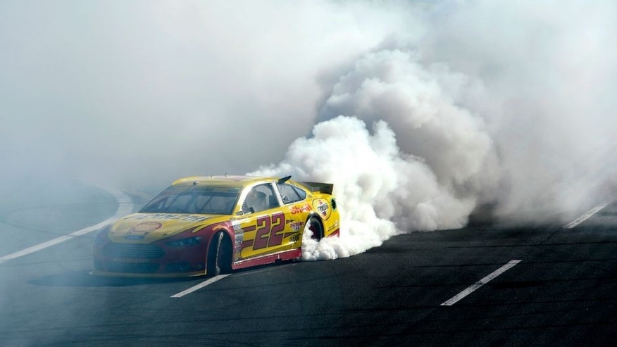 CHARLOTTE, NC - OCTOBER 11: Joey Logano, driver of the #22 Shell Pennzoil Ford, celebrates with a burnout after winning the NASCAR Sprint Cup Series Bank of America 500 at Charlotte Motor Speedway on October 11, 2015 in Charlotte, North Carolina. (Photo by Robert Laberge/NASCAR via Getty Images)
