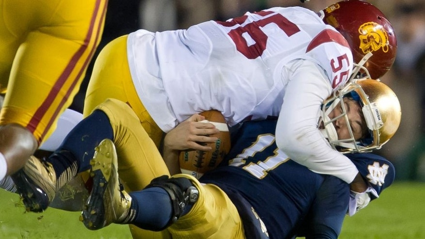 Oct 19, 2013; South Bend, IN, USA; Notre Dame Fighting Irish quarterback Tommy Rees (11) is sacked by USC Trojans linebacker Lamar Dawson (55) in the third quarter at Notre Dame Stadium. Notre Dame won 14-10. Mandatory Credit: Matt Cashore-USA TODAY Sports
