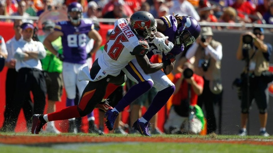 Oct 26, 2014; Tampa, FL, USA; Minnesota Vikings wide receiver Cordarrelle Patterson (84) runs with the ball as Tampa Bay Buccaneers cornerback Crezdon Butler (26) defends during the first half at Raymond James Stadium. Mandatory Credit: Kim Klement-USA TODAY Sports
