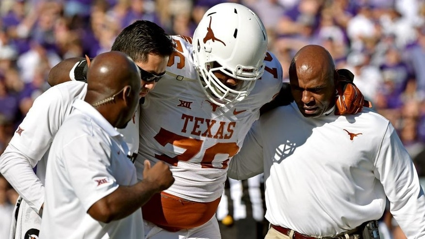 MANHATTAN, KS - OCTOBER 25: Head coach Charlie Strong (R) of the Texas Longhorns helps trainers take offensive guard Kent Perkins #76 against the Kansas State Wildcats during the first half on October 25, 2014 at Bill Snyder Family Stadium in Manhattan, Kansas. (Photo by Peter G. Aiken/Getty Images)