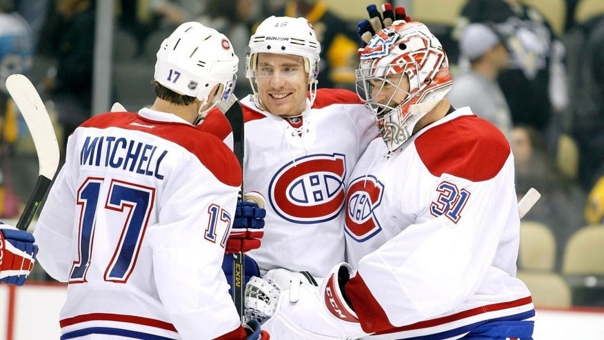 PITTSBURGH, PA - OCTOBER 13: Carey Price #31 of the Montreal Canadiens celebrates with Tomas Fleischmann #15 and Torrey Mitchell #17 after defeating the Pittsburgh Penguins 3-2 at Consol Energy Center on October 13, 2015 in Pittsburgh, Pennsylvania. (Photo by Justin K. Aller/Getty Images)