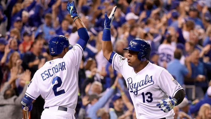 KANSAS CITY, MO - OCTOBER 14: Salvador Perez #13 of the Kansas City Royals celebrates with teammate Alcides Escobar #2 after scoring on the RBI double hit by Alex Rios #15 in the bottom of the fifth inning of Game 5 of the ALDS against the Houston Astros at Kauffman Stadium on Wednesday, October 14, 2015 in Kansas City Missouri. (Photo by LG Patterson/MLB Photos via Getty Images)
