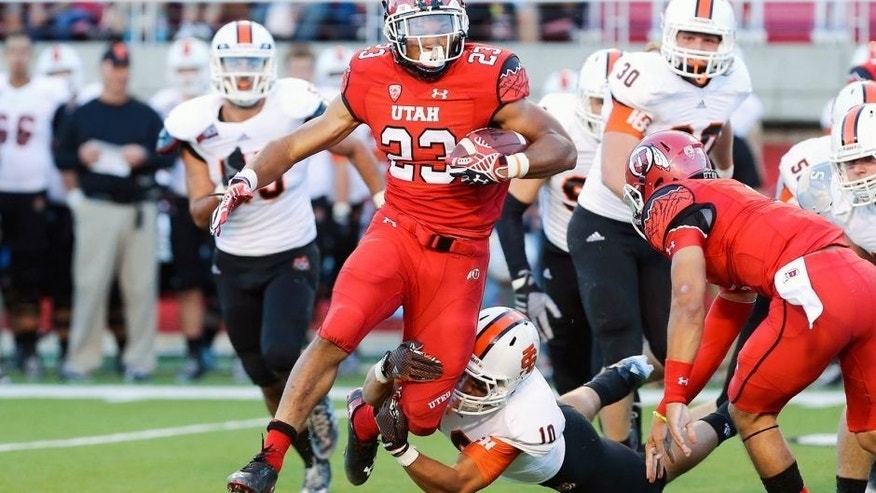 Aug 28, 2014; Salt Lake City, UT, USA; Utah Utes running back Devontae Booker (23) carries the ball as Idaho State Bengals defensive back Taison Manu (10) chases during the third quarter at Rice-Eccles Stadium. The Utes won 56-14. Mandatory Credit: Chris Nicoll-USA TODAY Sports