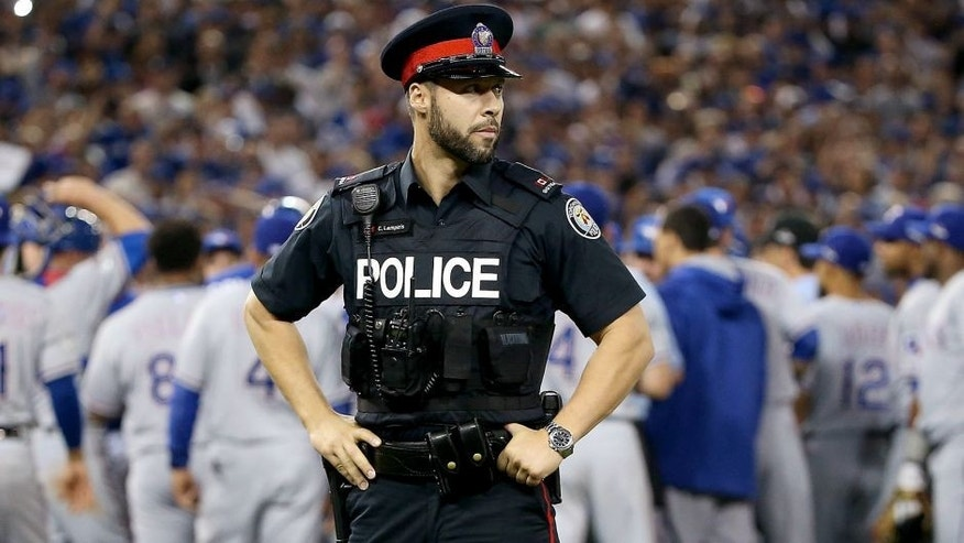 TORONTO, ON - OCTOBER 14: As the benches clear a Toronto police officer is seen in game five of the American League Division Series between the Texas Rangers and the Toronto Blue Jays at Rogers Centre on October 14, 2015 in Toronto, Canada. (Photo by Tom Szczerbowski/Getty Images)