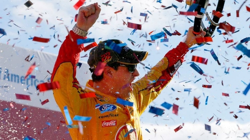 CHARLOTTE, NC - OCTOBER 11: Joey Logano, driver of the #22 Shell Pennzoil Ford, celebrates in Victory Lane after winning the NASCAR Sprint Cup Series Bank of America 500 at Charlotte Motor Speedway on October 11, 2015 in Charlotte, North Carolina. (Photo by Jonathan Ferrey/Getty Images)