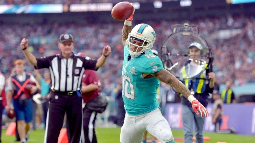 Oct 4, 2015; London, United Kingdom; Miami Dolphins receiver Kenny Stills (10) spikes the ball in celebration after scoring on a 10-yard touchdown reception in the fourth quarter against the New York Jets in Game 12 of the NFL International Series at Wembley Stadium. The Jets defeated the Dolphins 27-14. Mandatory Credit: Kirby Lee-USA TODAY Sports