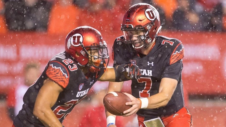 Oct 17, 2015; Salt Lake City, UT, USA; Utah Utes quarterback Travis Wilson (7) hands off to running back Devontae Booker (23) during the first half against the Arizona State Sun Devils at Rice-Eccles Stadium. Mandatory Credit: Russ Isabella-USA TODAY Sports