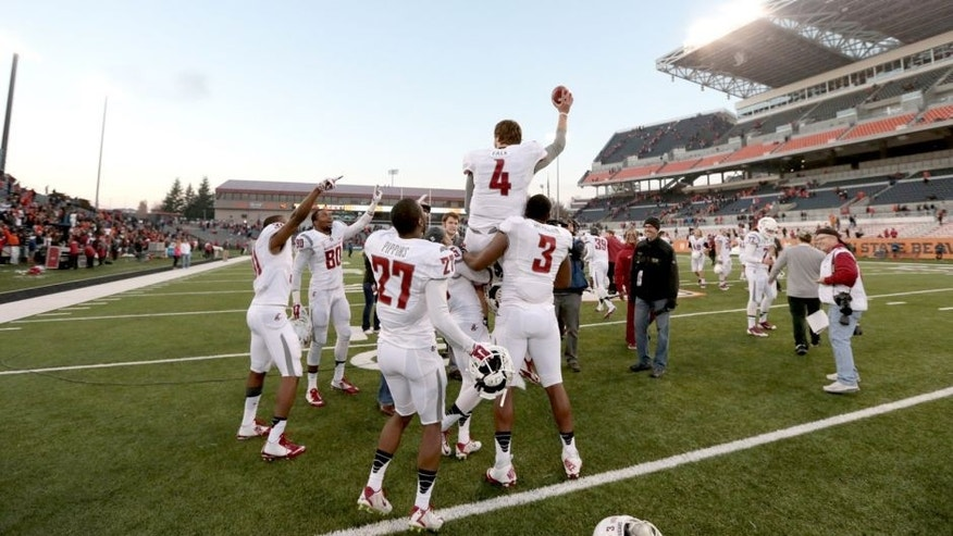 Nov 8, 2014; Corvallis, OR, USA; Washington State Cougars quarterback Luke Falk (4) is lifted into the air by linebacker Ivan McLennan (3) and wide receiver Rickey Galvin (5) following a win against the Oregon State Beavers against the Oregon State Beavers at Reser Stadium. Mandatory Credit: Scott Olmos-USA TODAY Sports