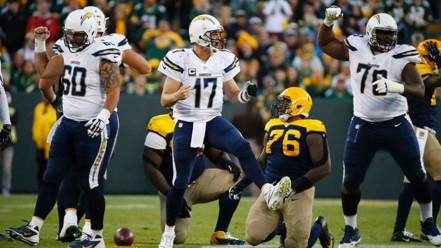 San Diego Chargers quarterback Philip Rivers (center) celebrates with teammates after the Green Bay Packers were given a penalty on fourth down during the second half Sunday, Oct. 18, 2015, in Green Bay, Wis.