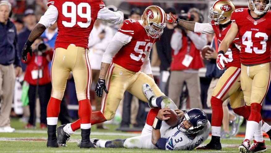 Nov 27, 2014; Santa Clara, CA, USA; Seattle Seahawks quarterback Russell Wilson (3) lays on the ground after being tackled by San Francisco 49ers outside linebacker Aaron Lynch (59) in the third quarter at Levi's Stadium. The Seahawks defeated the 49ers 19-3. Mandatory Credit: Cary Edmondson-USA TODAY Sports