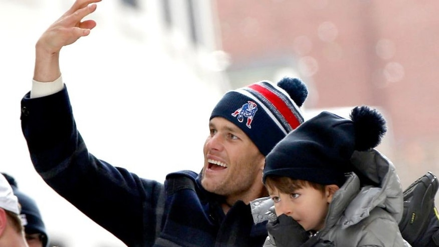 Feb 4, 2015; Boston, MA, USA; New England Patriots quarterback Tom Brady (12) and his son during the Super Bowl XLIX-New England Patriots Parade. Mandatory Credit: Greg M. Cooper-USA TODAY Sports
