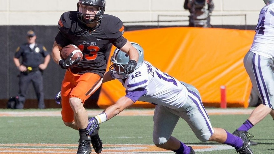 Oct 5, 2013; Stillwater, OK, USA; Oklahoma State Cowboys wide receiver David Glidden (13) runs for yardage during the second quarter against Kansas State Wildcats defensive back Ty Zimmerman (12) at Boone Pickens Stadium. Mandatory Credit: Richard Rowe-USA TODAY Sports