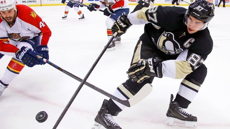 Florida Panthers' Erik Gudbranson (44) knocks the puck off the stick of Pittsburgh Penguins' Sidney Crosby (87) during the second period of an NHL hockey game in Pittsburgh Tuesday, Oct. 20, 2015.(AP Photo/Gene J. Puskar)