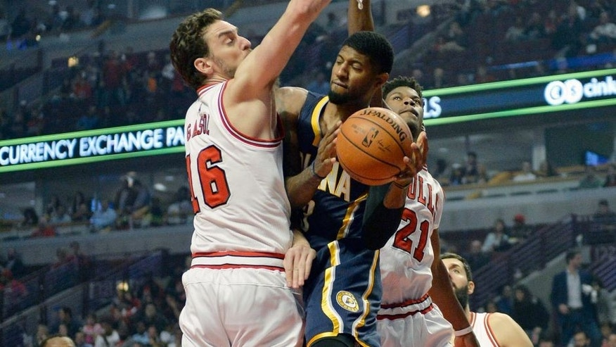 Indiana Pacers' Paul George (13), passes around Chicago Bulls' Pau Gasol (16), and Jimmy Butler (21), during the first half of an NBA preseason basketball game Tuesday, Oct. 20, 2015, in Chicago. (AP Photo/Paul Beaty)