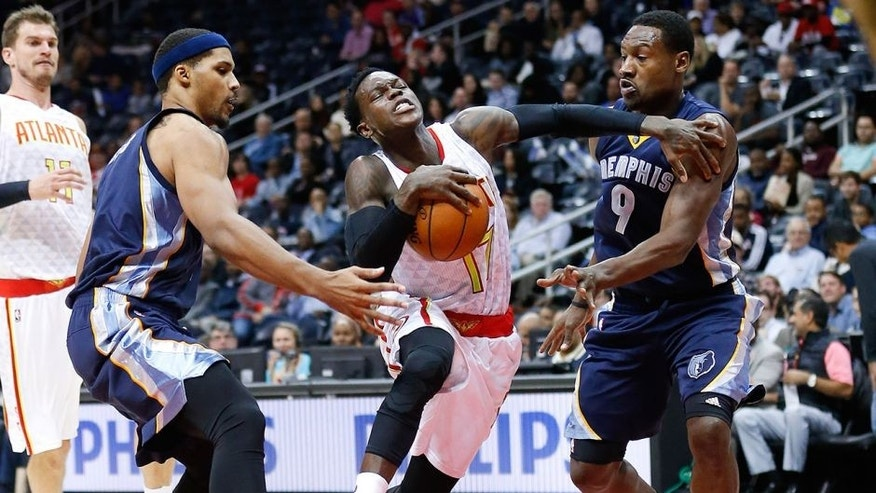 Atlanta Hawks guard Dennis Schroder (17) drives between Memphis Grizzlies' Jarnell Stokes (1) and Tony Allen (9) in the first half of an NBA basketball game Wednesday, Oct. 21, 2015, in Atlanta. (AP Photo/John Bazemore)