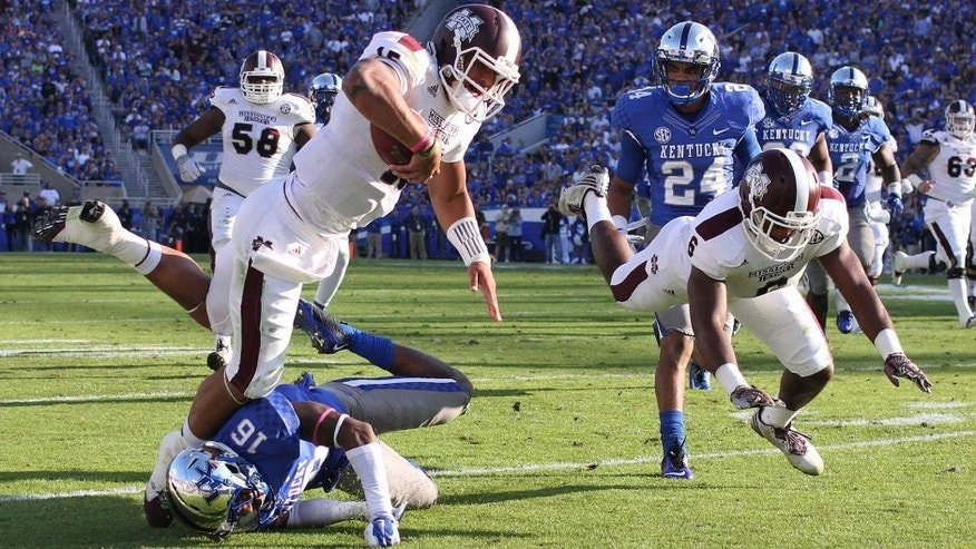 Oct 25, 2014; Lexington, KY, USA; Mississippi State Bulldogs quarterback Dak Prescott (15) runs the ball against Kentucky Wildcats cornerback Cody Quinn (16) in the first half at Commonwealth Stadium. Mandatory Credit: Mark Zerof-USA TODAY Sports