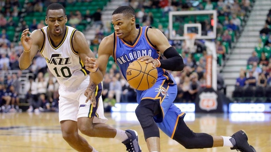 Oklahoma City Thunder guard Russell Westbrook, right, drives around Utah Jazz guard Alec Burks during the second half of an NBA preseason basketball game Tuesday, Oct. 20, 2015, in Salt Lake City. The Thunder won 113-102. (AP Photo/Rick Bowmer)