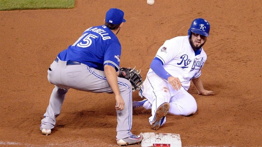 Oct 23, 2015; Kansas City, MO, USA; Kansas City Royals third baseman Mike Moustakas (8) slides back to first base ahead of the throw to Toronto Blue Jays first baseman Chris Colabello (15) in the 7th inning in game six of the ALCS at Kauffman Stadium. Mandatory Credit: John Rieger-USA TODAY Sports