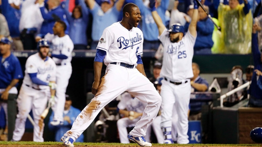 Kansas City Royals' Lorenzo Cain celebrates after scoring on a hit by Eric Hosmer against the Toronto Blue Jays during the eight inning in Game 6 of baseball's American League Championship Series on Friday, Oct. 23, 2015, in Kansas City, Mo.
