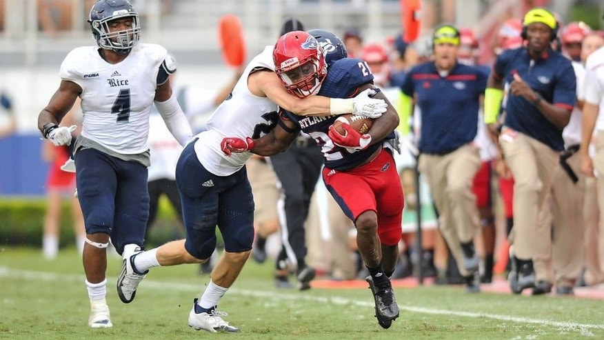 Oct 10, 2015; Boca Raton, FL, USA; Florida Atlantic Owls running back Marcus Clark (20) runs is tackled by Rice Owls cornerback Jorian Clark (20) during the second half at FAU Football Stadium. Mandatory Credit: Steve Mitchell-USA TODAY Sports