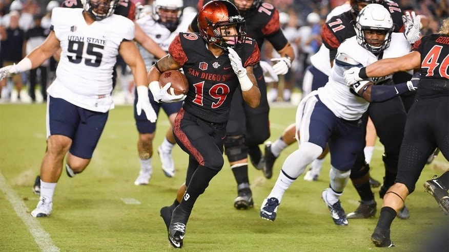 San Diego State running back Donnel Pumphrey (19) carries past the Utah State defense during the first half of an NCAA college football game Friday, Oct. 23, 2015 in San Diego. (AP Photo/Denis Poroy)