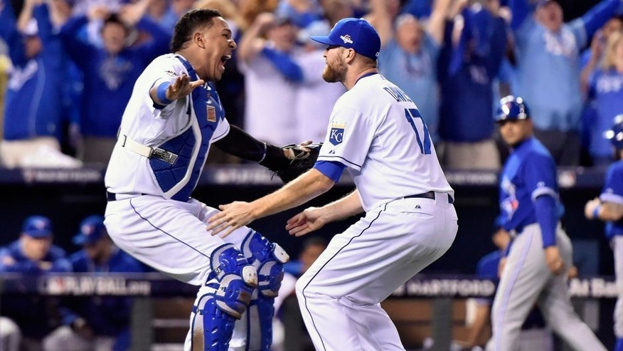 Kansas City Royals catcher Salvador Perez, left, and relief pitcher Wade Davis celebrate after defeating the Toronto Blue Jays in Game 6 of baseball's American League Championship Series on Friday, Oct. 23, 2015, in Kansas City, Mo. The Royals won 4-3. (Nathan Denette/The Canadian Press via AP) MANDATORY CREDIT