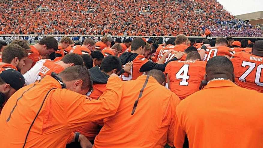 Oklahoma State players and staff form a prayer circle prior to an NCAA college football game between Kansas and Oklahoma St in Stillwater, Okla., Saturday, Oct. 24, 2015. Earlier in the day tragedy struck at the Oklahoma State homecoming parade as a car ran into a group of parade watchers killing at least three and injuring dozens more. (AP Photo/Brody Schmidt)