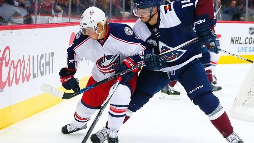 Colorado Avalanche left wing Blake Comeau (14) and Columbus Blue Jackets right wing Cam Atkinson (13) chase the puck during the second period of an NHL hockey game Saturday, Oct. 24, 2015, in Denver. (AP Photo/Jack Dempsey)