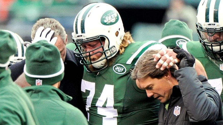 New York Jets center Nick Mangold (74) is helped off the field after being hurt during the first half of an NFL football game against the New England Patriots, Sunday, Dec. 21, 2014, in East Rutherford, N.J. (AP Photo/Bill Kostroun)