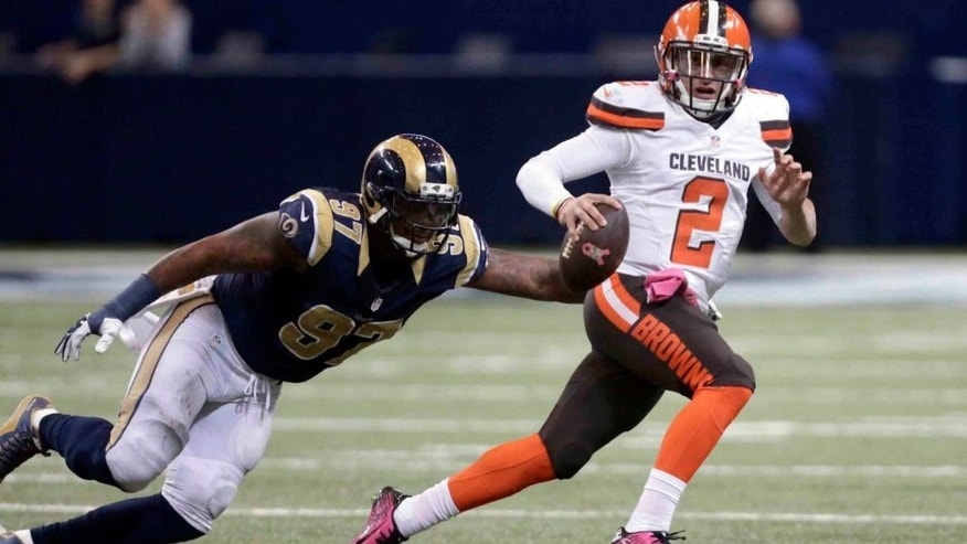 Cleveland Browns quarterback Johnny Manziel, right, runs with the ball as St. Louis Rams defensive end Eugene Sims pursues during the fourth quarter of an NFL football game Sunday, Oct. 25, 2015, in St. Louis. The Rams won 24-6. (AP Photo/Tom Gannam)
