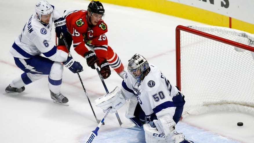Chicago Blackhawks center Jonathan Toews (19) scores a game winning goal past Tampa Bay Lightning goalie Kristers Gudlevskis and defenseman Anton Stralman (6) during overtime in an NHL hockey game in Chicago, Saturday, Oct. 24, 2015. Chicago won 1-0. (AP Photo/Andrew A. Nelles)