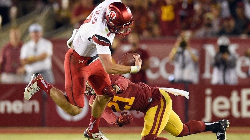 Oct 24, 2015; Los Angeles, CA, USA; Utah Utes quarterback Travis Wilson (left) is tackled by Southern California Trojans outside linebacker Su'a Cravens (right) during the fourth quarter at Los Angeles Memorial Coliseum. The Southern California Trojans won 42-24. Mandatory Credit: Kelvin Kuo-USA TODAY Sports